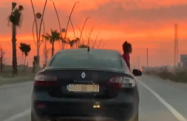 Seyir halindeki aracın camından sarkan çocuk korkuttu