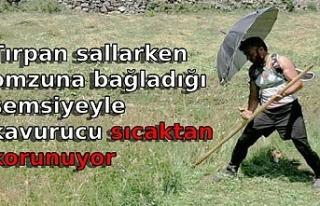 Tırpan sallarken omzuna bağladığı şemsiyeyle...